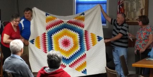 Brian and others holding quilt